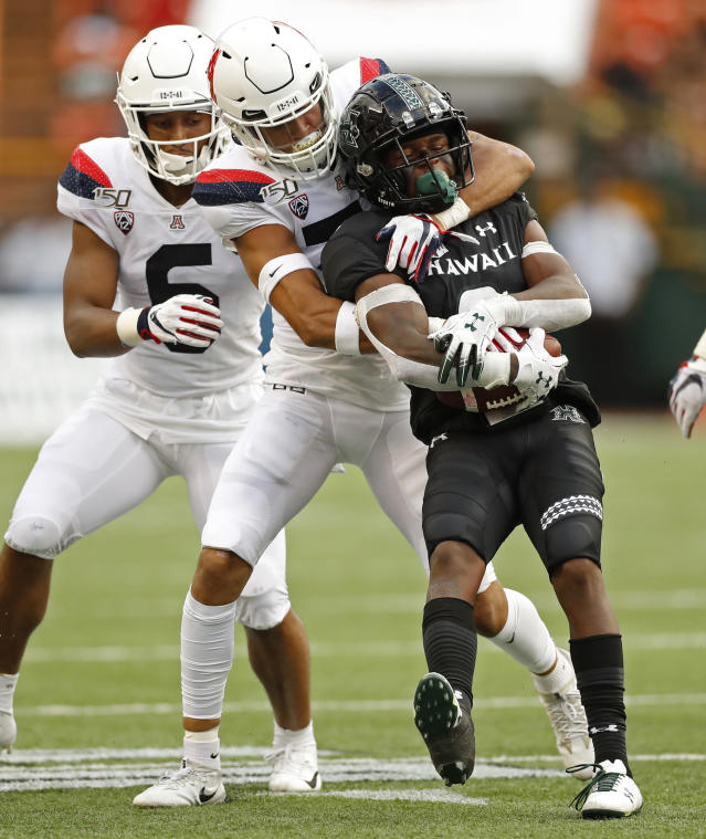 Arizona safety Scottie Young Jr. (6) watches as linebacker Colin Schooler (7) pulls down Hawaii wide receiver Cedric Byrd II (6) during the first half of an NCAA college football game Saturday, Aug. 24, 2019, in Honolulu. (AP Photo/Marco Garcia)