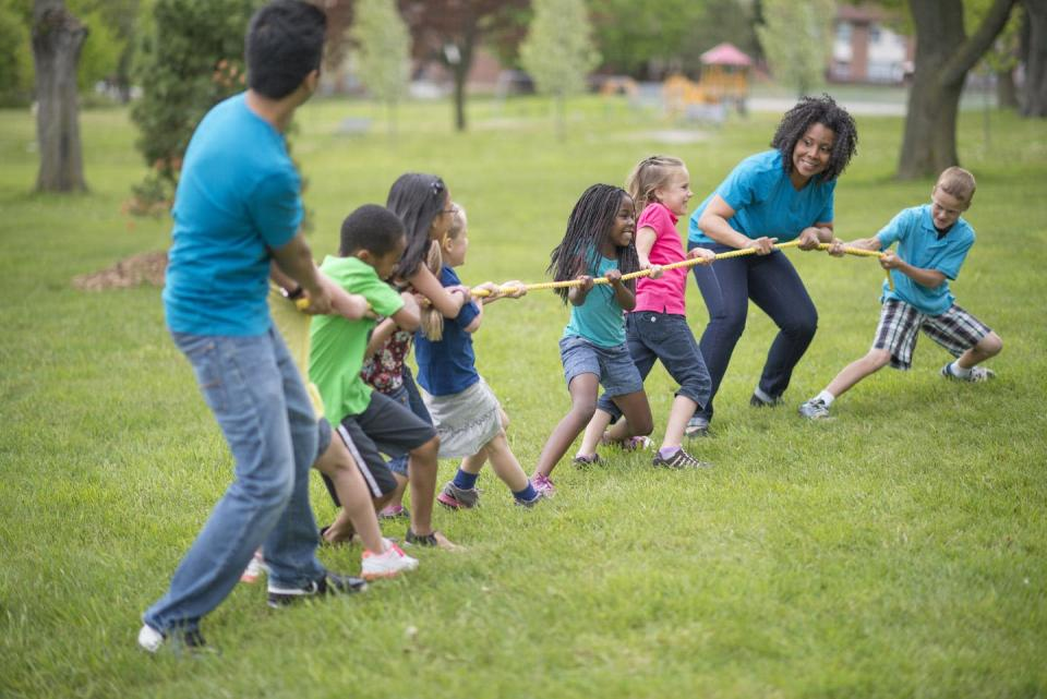 A multi-ethnic group of elementary age children are playing tug-of-war with a rope at the park.