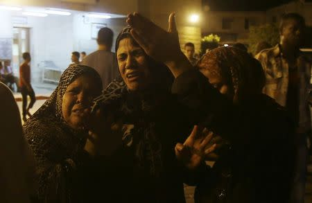 Women mourn after an Israeli air strike killed two Palestinian militants, at a hospital morgue in the central Gaza Strip July 6, 2014. REUTERS/Ibraheem Abu Mustafa
