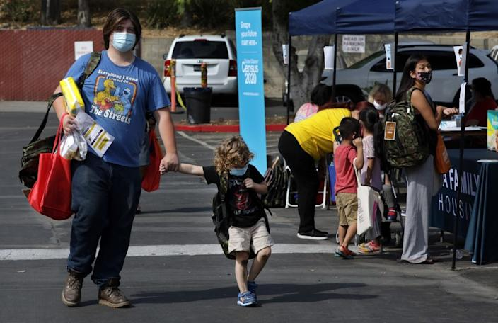 SYLMAR, CA - AUGUST 17: Ian Roistacher and his brother Mitch Roistacher, 4, walk back to their hotel room after picking up back-to-school supplies for Ian's three younger brothers during a fair at the Vagabond Inn in Sylmar on Monday, Aug. 17, 2020. The event, on the first day of school, was a partnership between Councilwoman Monica Rodriguez and L.A. Family Housing providing students with backpacks full of school supplies and other essential items for the family. The families participating are those facing economic hardship because of the pandemic. (Myung J. Chun / Los Angeles Times)