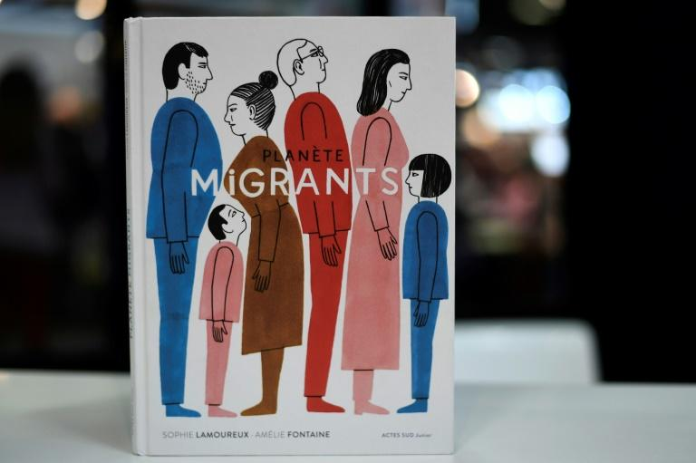 "The French book ""Planete Migrants"" by Sophie Lamoureux and Amelie Fontaine is on display at the International Children's book fair on April 5, 2017 in Bologne"
