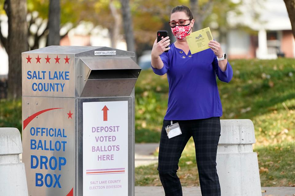 Jennifer Fresques takes a selfie before inserting her ballot into an official ballot drop box Tuesday, Oct. 20, 2020, in Salt Lake City.