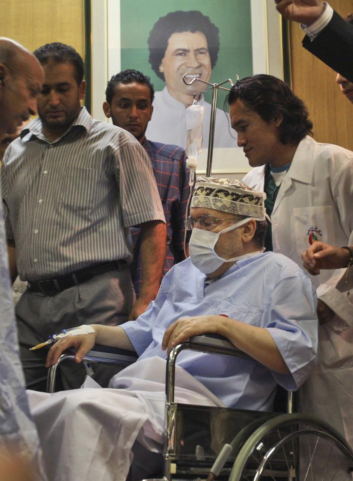 FILE - In this Sept. 9, 2009 file photo, Libyan Abdel Baset al-Megrahi, the only man convicted in the 1988 Lockerbie bombing, is wheeled past a portrait of Libyan leader Moammar Gadhafi at the international hospital in Tripoli, Libya. The Dec. 21, 1988 explosion would quickly transform the Scottish town into a byword for international terror. Now it is being remembered again because of the 2011 conflict in Libya, the country that accepted responsibility for blowing up Pan Am Flight 103.