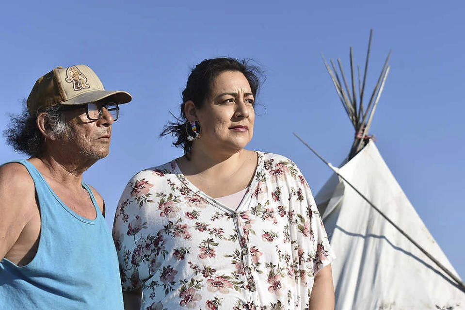 In this Thursday, May 20, 2021, photo, Fawn Wasin Zi, right, poses with her father, Terry Yellow Fat, in front of a tent on the Standing Rock Sioux Reservation in Fort Yates, North Dakota. The pipeline fight stirs bitter memories in Fawn Wasin Zi, a biology teacher who chairs the Standing Rock renewable energy power authority. (AP Photo/Matthew Brown)