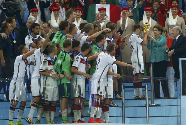 Brazil's President Dilma Rousseff (R) hands the World Cup trophy over to Germany's captain Philipp Lahm (2nd R) after the 2014 World Cup final against Argentina at the Maracana stadium in Rio de Janeiro July 13, 2014. REUTERS/Eddie Keogh (BRAZIL - Tags: SOCCER SPORT WORLD CUP TPX IMAGES OF THE DAY)