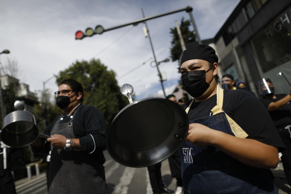 "Restaurant workers bang metal pots as more than a hundred employees from multiple restaurants blocked a street in the Polanco neighborhood to protest against COVID-19 ""red alert"" restrictions that have closed on-site dining, in Mexico City, Tuesday, Jan. 12, 2021. More than three weeks into Mexico City's second pandemic shutdown, restaurateurs desperate to save their businesses and maintain their employees are uniting under the slogan ""Open or Die"" (""Abrir o morir"" in Spanish), to pressure the city government to allow them to operate with limited seating and protective health measures. (AP Photo/Rebecca Blackwell)"