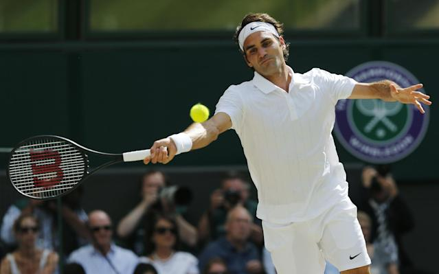 Roger Federer of Switzerland plays a return to Novak Djokovic of Serbia during their men's singles final match at the All England Lawn Tennis Championships in Wimbledon, London, Sunday, July 6, 2014. (AP Photo/Ben Curtis)