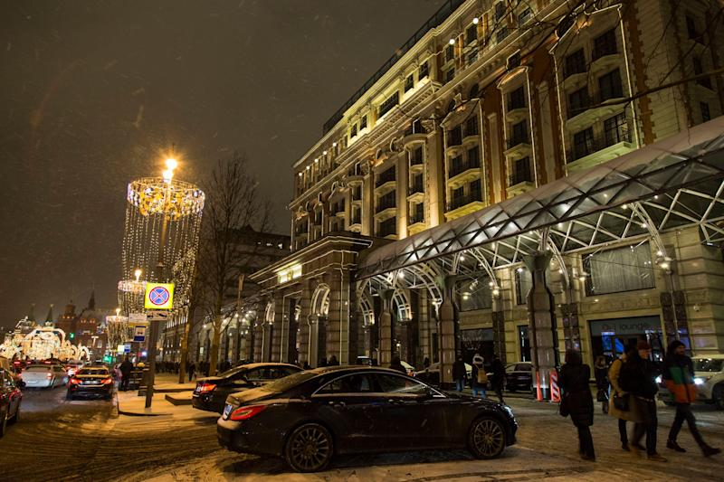 In this photo taken on Monday, Feb. 13, 2017, people walk past the Ritz-Carlton hotel, right, with Red Square behind in the background left, in Moscow, Russia. Despite saying he wanted to build a Trump tower in Russia, Donald Trump, who stayed at the Ritz in 2013, never completed a deal in the country's booming _ but volatile _ real estate and hotel market. (AP Photo/Alexander Zemlianichenko)