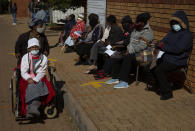 FILE - In this June 3, 2021, file photo, an elderly woman leaves as others wait to receive the Pfizer COVID-19 vaccine, at a clinic at Orange Farm, near Johannesburg. South Africa imposed tighter restrictions on public gatherings and liquor sales as hospital admissions due to COVID-19 increased by 59% over the past two weeks, President Cyril Ramaphosa said on Tuesday, June 15. New cases there have nearly doubled. (AP Photo/Denis Farrell, File)