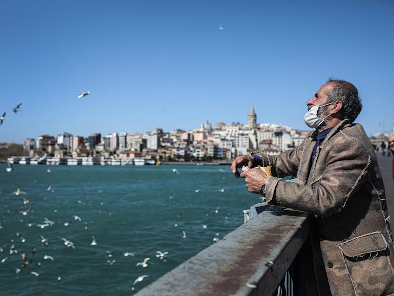 A man wearing face mask feeds seagulls from nearly empty Galata Bridge as people are staying home due to the coronavirus pandemic in Istanbul, Turkey on April 7.