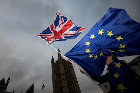 An Anti-Brexit protestor waves EU and Union flags outside the Houses of Parliament