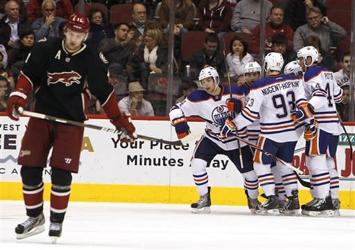 Edmonton Oilers' Taylor Hall (4) skates away from his teammates Ryan Nugent-Hopkins (93), Corey Potter (44), Jordan Eberle (14), and Shawn Horcoff after a Hall goal, while Phoenix Coyotes' Martin Hanzal, of the Czech Republic, left, skates away from the action in the second period in an NHL hockey game Thursday, Dec. 15, 2011, in Glendale, Ariz.(AP Photo/Ross D. Franklin)