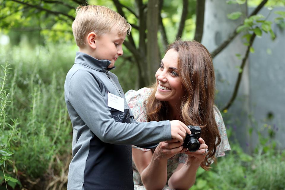 The Duchess of Cambridge speaks with Josh Evans during a visit to a Royal Photographic Society workshop with Action for Children which uses photography to help young people develop confidence and self-expression, at Warren Park Children's Centre, Kingston upon Thames.
