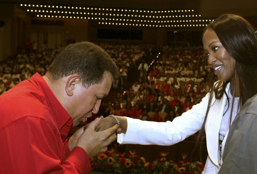In this photo released by Miraflores Press Office, Venezuela's President Hugo Chavez, left, kisses the hand of British top model Naomi Campbell during a ceremony in which several Venezuelan women, considered 'Heroes of the Revolution' will be decorated, including Hugo Chavez's daughter, Maria Gabriela Chavez, in Caracas, Wednesday, Oct. 31, 2007. (AP Photo/Miraflores Press Office) **  NO SALES  **