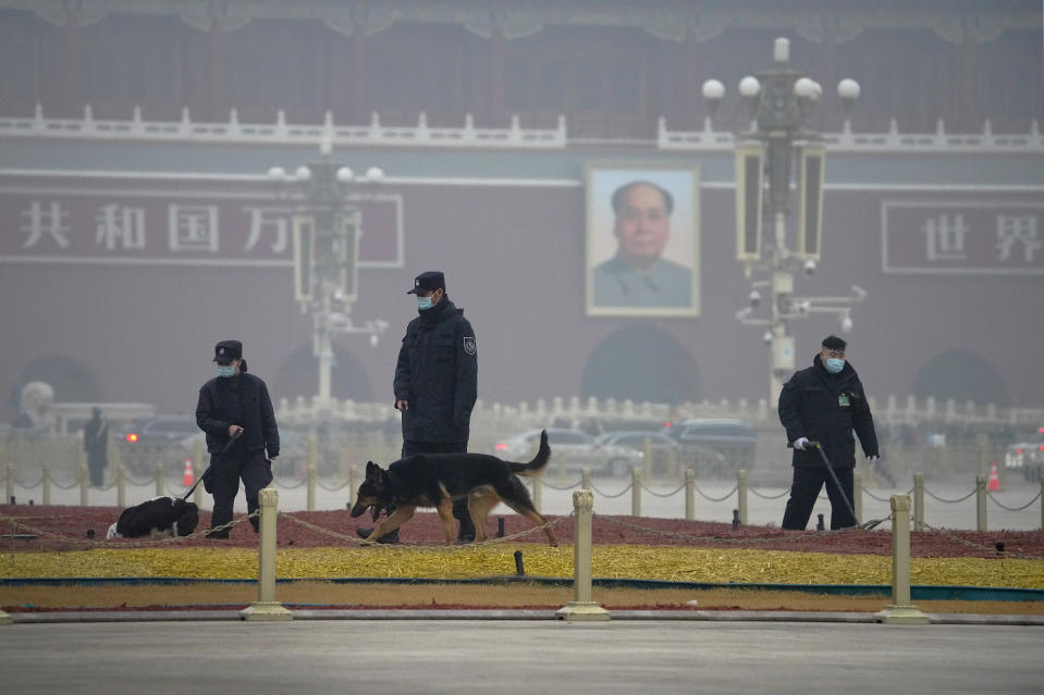 Police officers use sniffer dogs to check on Tiananmen Square before delegates arrive for the opening session of China's National People's Congress (NPC) at the Great Hall of the People in Beijing, Friday, March 5, 2021. China's No. 2 leader has set a healthy economic growth target and vowed to make this nation self-reliant in technology amid tension with Washington and Europe over trade and human rights. (AP Photo/Andy Wong)