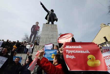Opposition supporters hold posters and a cutout figure depicting Prime Minister Dmitry Medvedev during a rally in front of a monument of Soviet state founder Vladimir Lenin in Vladivostok. The poster on the right reads: Pathetic. Cowardly. Thief.    REUTERS/Yuri Maltsev