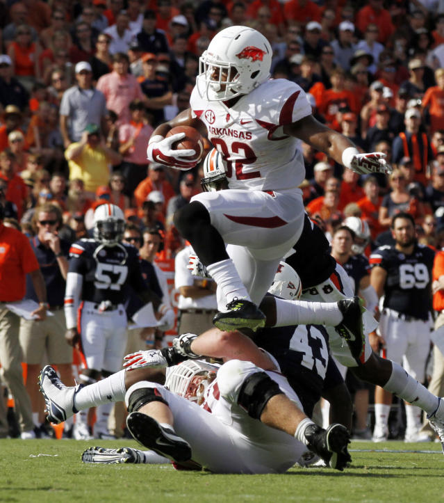 Arkansas running back Jonathan Williams (32) hurdles a pile of players as he carries the ball for a first down against Auburn during the first half of an NCAA college football game on Saturday, Aug. 30, 2014, in Auburn, Ala. (AP Photo/Butch Dill)