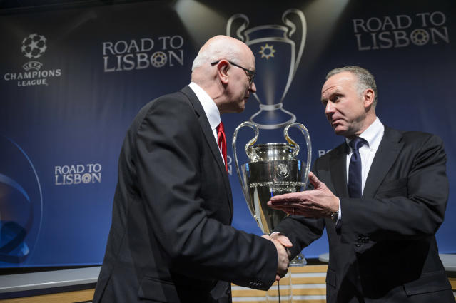 Arsenal club secretary David Miles, left, shakes hands with Bayern Munich CEO Karl-Heinz Rummenigge, right, after the draw of the round of 16 games of UEFA Champions League 2013/14 at the UEFA Headquarters in Nyon, Switzerland, Monday, Dec. 16, 2013. (AP Photo/Keystone,Laurent Gillieron)