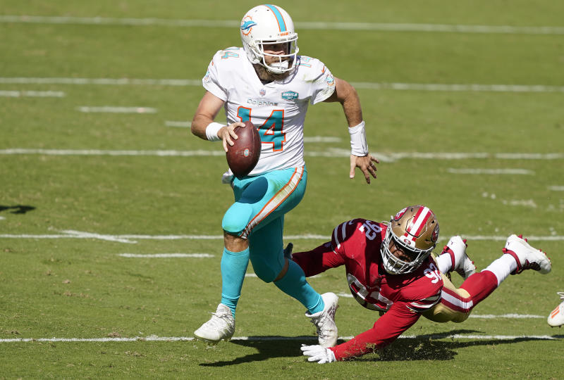 Dolphins quarterback Ryan Fitzpatrick avoids a tackle while looking to throw.