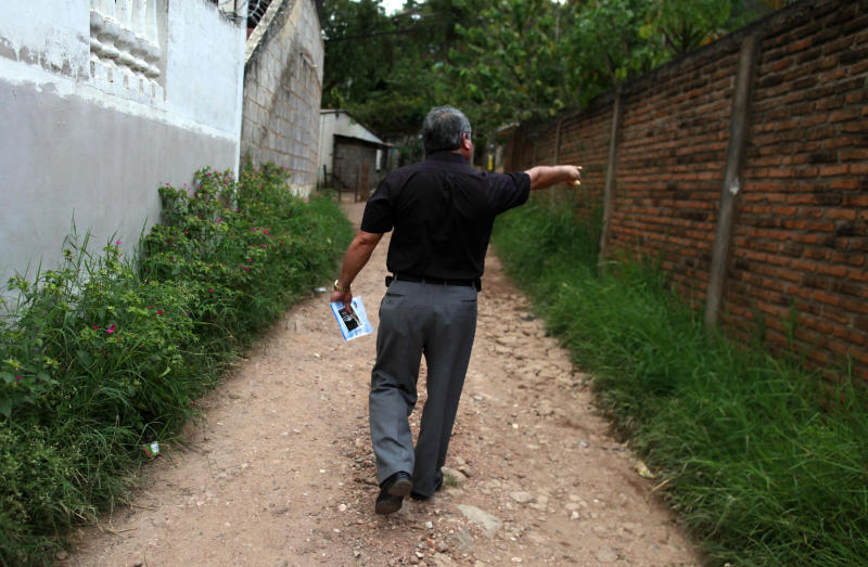 In this photo taken on Wednesday, Oct 17, 2012, Wilfredo Yanez, points at a bullet mark on a wall at the site where his late son Jaasiel Yanez, 15, was shot dead allegedly by soldiers in Tegucigalpa, Honduras. According to his relatives, Jaasiel was killed by soldiers early Sunday, May 27, when he was riding a motorcycle, near a military checkpoint, allegedly accompanied by a young woman. (AP Photo/Esteban Felix)