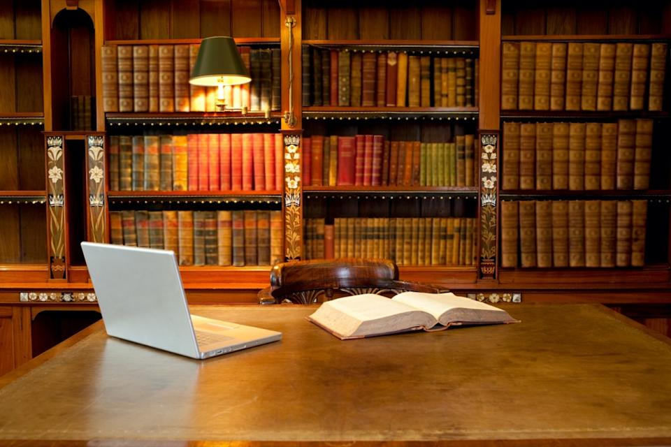 Laptop and book lying on a desk in classic library
