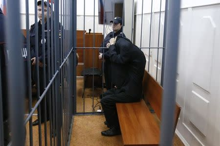 Abror Azimov, a suspect over the recent bombing of a metro train in St. Petersburg, covers his face inside the defendant's cage as he attends a court hearing in Moscow, Russia, April 18, 2017. REUTERS/Sergei Karpukhin