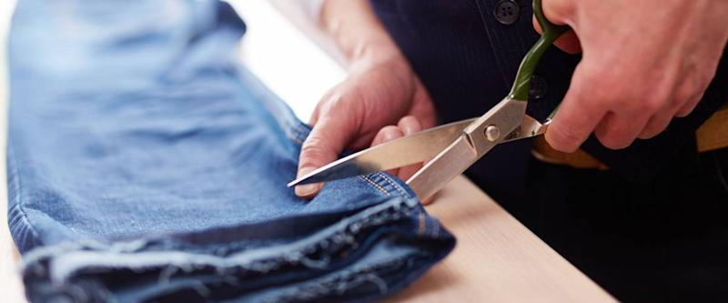 Closeup of tailors hands cutting jeans pants with big metal scissors on table in atelier