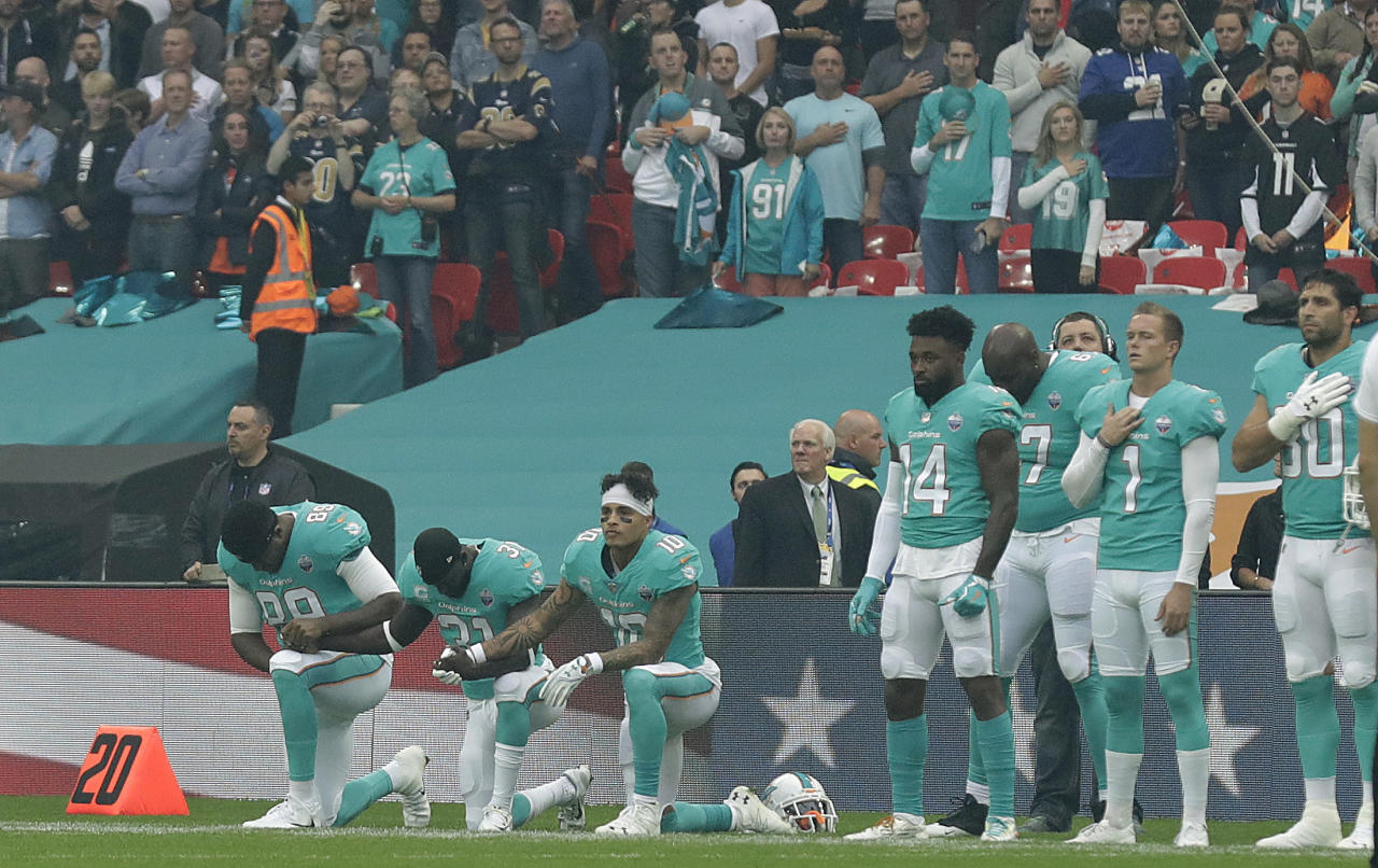 <p>Miami Dolphins' Julius Thomas (89), Michael Thomas (31) and Kenny Stills take a knee as the U.S. national anthem is played before an NFL football game against the New Orleans Saints at Wembley Stadium in London, Sunday Oct. 1, 2017. (AP Photo/Matt Dunham) </p>