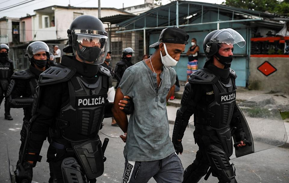 TOPSHOT - A man is arrested during a demonstration against the government of President Miguel Diaz-Canel in Arroyo Naranjo Municipality, Havana on July 12, 2021. - Cuba on Monday blamed a
