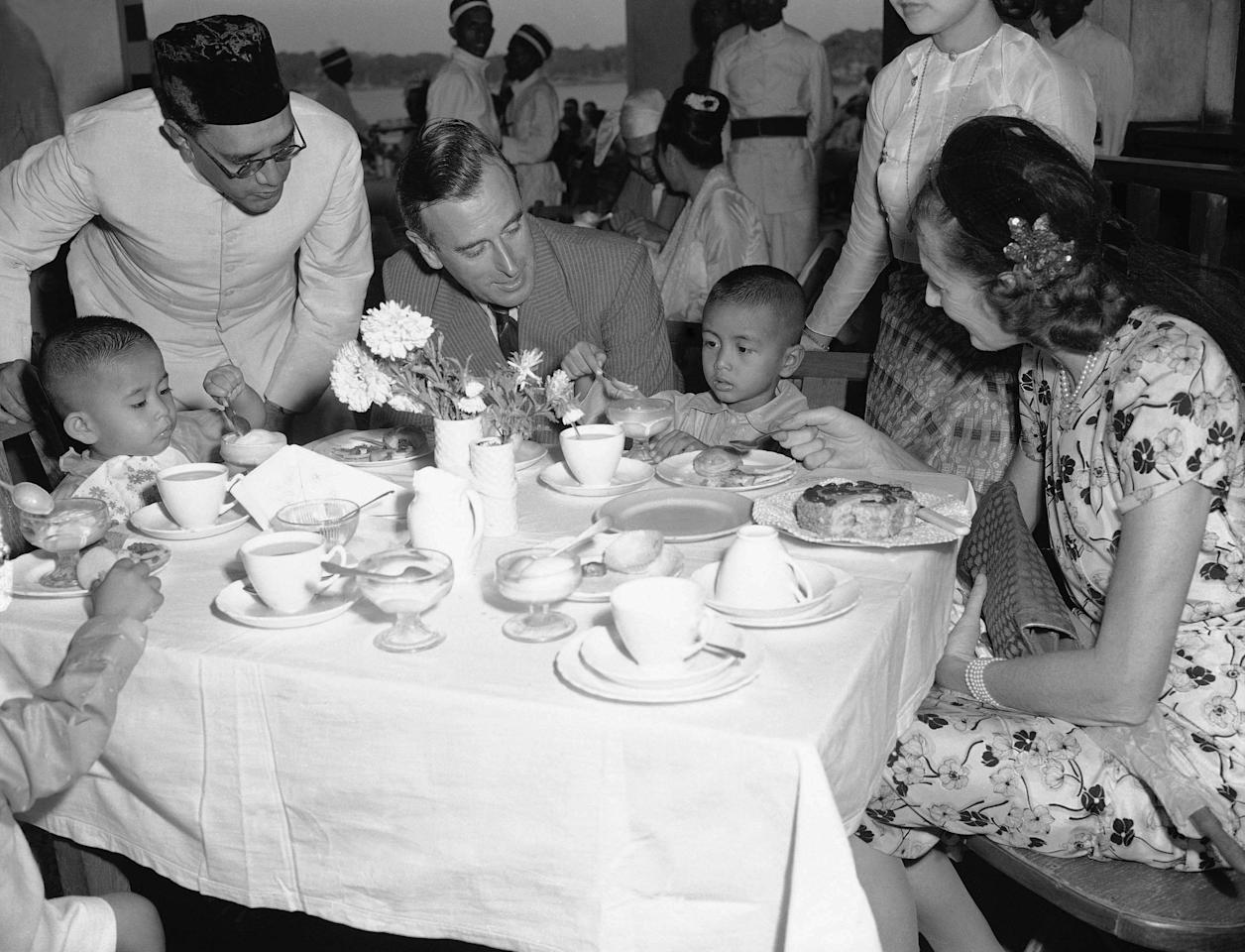 FILE - In this March 22, 1948 file photo, Lord Louis Mountbatten, governor general of India, center left, and his wife Edwina, right, watch as Aung San Suu Kyi, left, 2, and Aung San U, 4, eat ice cream at a party at the boat club in Rangoon, Burma. The children's father, Gen. Aung San, was assassinated on July 19, 1947 after he was slated to be of a projected independent Burma. (AP Photo/MD)
