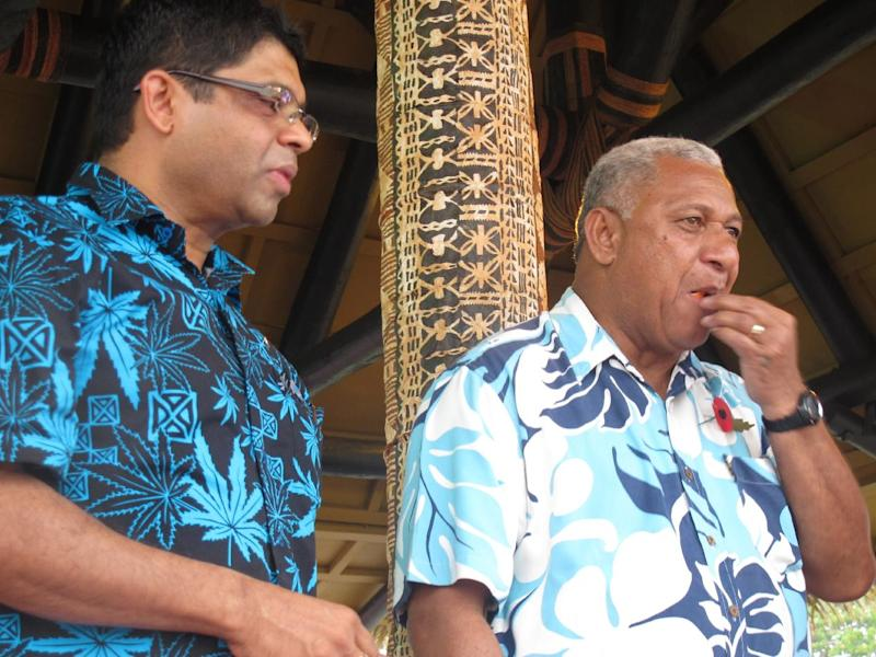 In this Nov. 7, 2013 photo, Fiji's Prime Minister Voreqe Bainimarama, right, and Attorney-General Aiyaz Sayed-Khaiyum, left, eat cake at the opening of a picnic park, in Suva, Fiji. Seven years after seizing power in a military coup, Bainimarama, the 59-year-old former naval officer, who also goes by the name Frank, has promised to hold democratic elections in this South Pacific island nation of 900,000. More than half a million Fijians have registered to vote, hoping to end a quarter-century of turmoil. The international community, which imposed sanctions after the coup, has offered a cautious welcome. (AP Photo/Nick Perry)