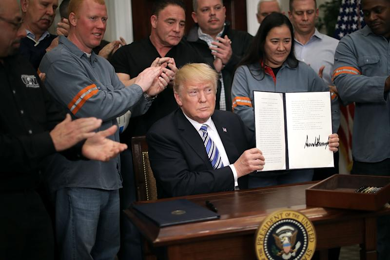 WASHINGTON, DC - MARCH 08: Surrounded by applauding steel and aluminum workers, U.S. President Donald Trump holds up the 'Section 232 Proclamation' on steel imports that he signed in Roosevelt Room the the White House March 8, 2018 in Washington, DC. Trump announced last week that he will impose a 25-percent tarriff on imported steel and a 10-percent tarriff on imported alumninum. (Photo by Chip Somodevilla/Getty Images)