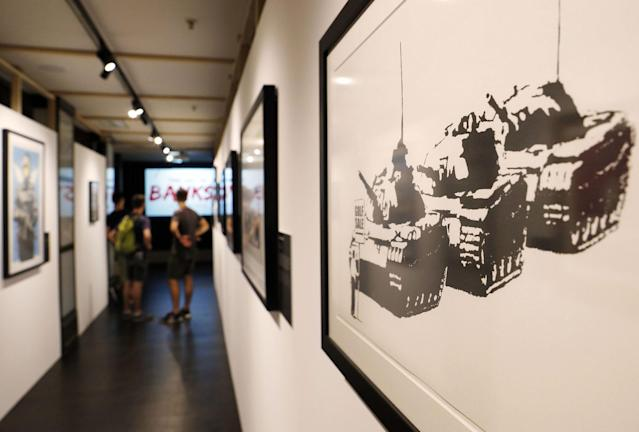 <p>A group of visitors walk through a corridor next to the artwork 'Golf Sale' by British Banksy during the exhibition 'The Art of Banksy' in Berlin, Germany on June 20, 2017. (Felipe Trueba/EPA/REX/Shutterstock) </p>
