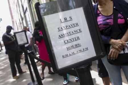 People wait outside the Internal Revenue Service office in the Brooklyn borough of New York