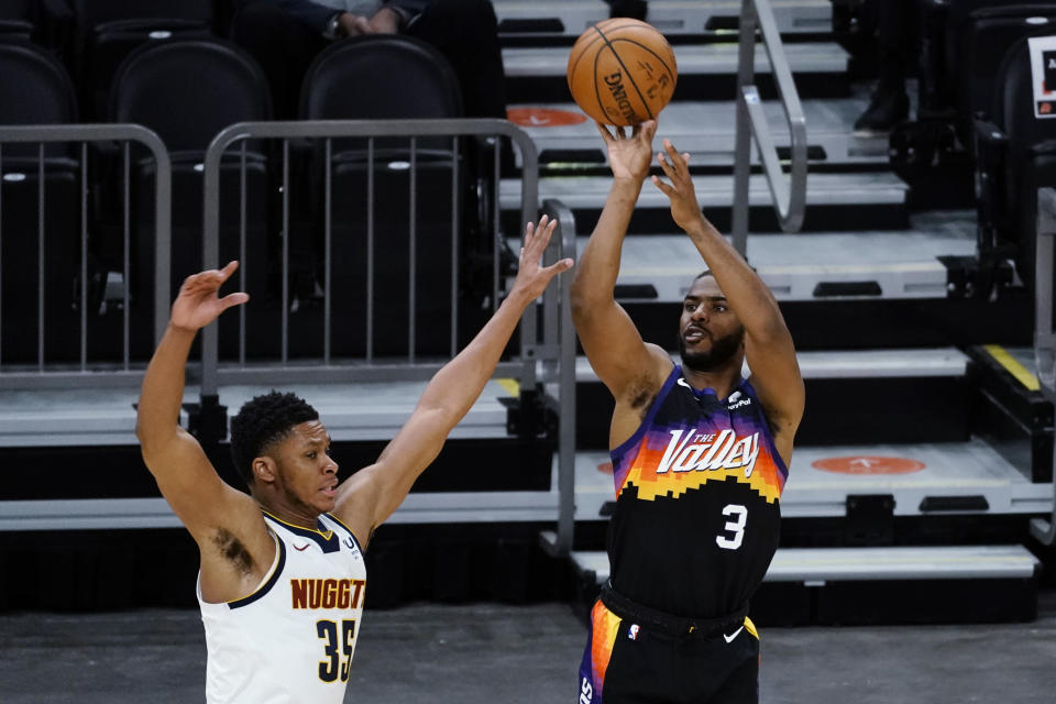 Phoenix Suns guard Chris Paul (3) shoots over Denver Nuggets guard PJ Dozier during the second half of an NBA basketball game Saturday, Jan. 23, 2021, in Phoenix. (AP Photo/Rick Scuteri)
