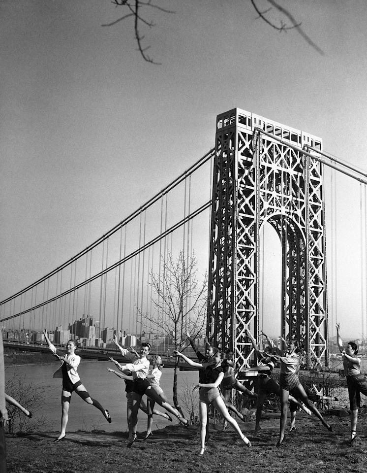 After hours of indoor practice, dancers from a New Jersey nightclub come outdoors to carry on their rehearsal in the spring air on the Jersey side of the George Washington Bridge, April 24, 1951. In the background is the bridge and the view of Manhattan looking north up the Hudson River, as they go through their routine on the Palisades Cliffs adjacent to the club, Bill Miller's Rendezvous, in preparation for the opening next month. (AP Photo/Robert Kradin)