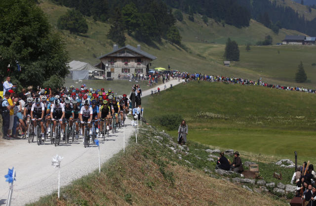 The pack rides on a gravel road during the tenth stage of the Tour de France cycling race over 158.8 kilometers (98.7 miles) with start in Annecy and finish in Le Grand-Bornand, France, Tuesday, July 17, 2018. (AP Photo/Peter Dejong)