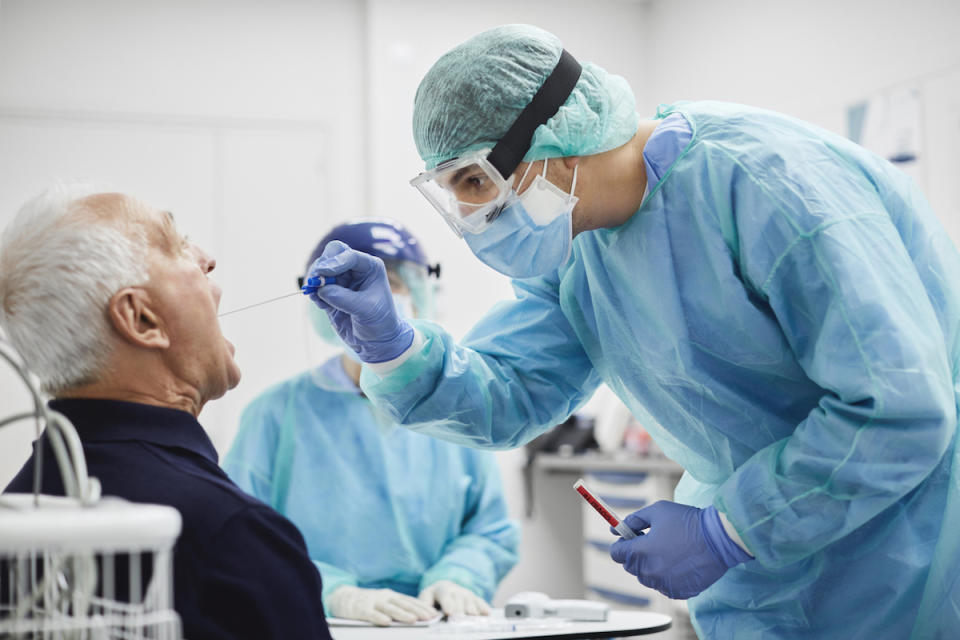 Doctor taking throat swab test from male patient
