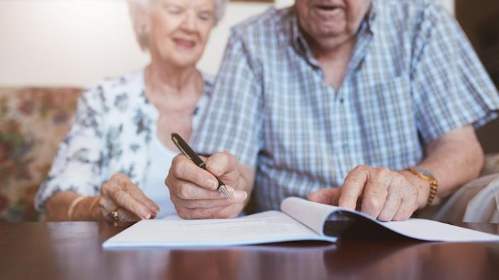 older senior couple signing a packet of documents