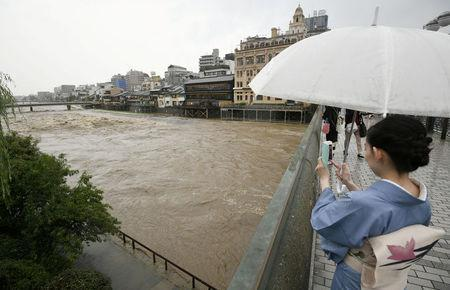 A kimono-clad woman using a smartphone takes photos of swollen Kamo River, caused by a heavy rain, from Shijo Bridge in Kyoto, western Japan, in this photo taken by Kyodo July 5, 2018. Mandatory credit Kyodo/via REUTERS