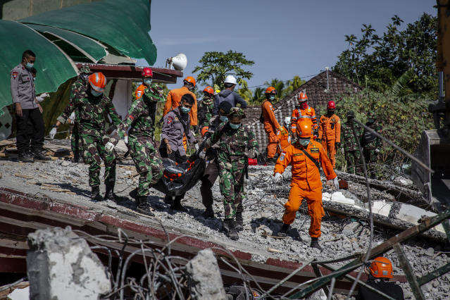 <p>Indonesian soldiers and search and rescue teams carry the body of a victim from a collapsed mosque following earthquake in Tanjung on Aug. 7, 2018 in Lombok Island, Indonesia. (Photo: Ulet Ifansasti/Getty Images) </p>