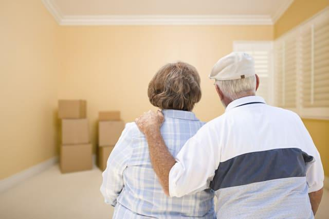 Senior Couple In Room Looking at Moving Boxes on Floor