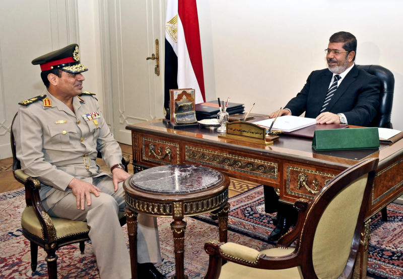 """FILE - In file this image released by the office of the Egyptian Presidency and taken on Wednesday, Aug. 22, 2012, Egyptian Minister of Defense, Lt. Gen. Abdel-Fattah el-Sissi, left, meets with Egyptian President Mohammed Morsi at the presidential palace in Cairo, Egypt. Egypt's military chief on Wednesday called on his countrymen to hold mass demonstrations to voice their support for the army and police to deal with potential """"violence and terrorism,"""" a move that signals a stepped up campaign against supporters of the ousted Islamist president. (AP Photo/Egyptian Presidency, File)"""