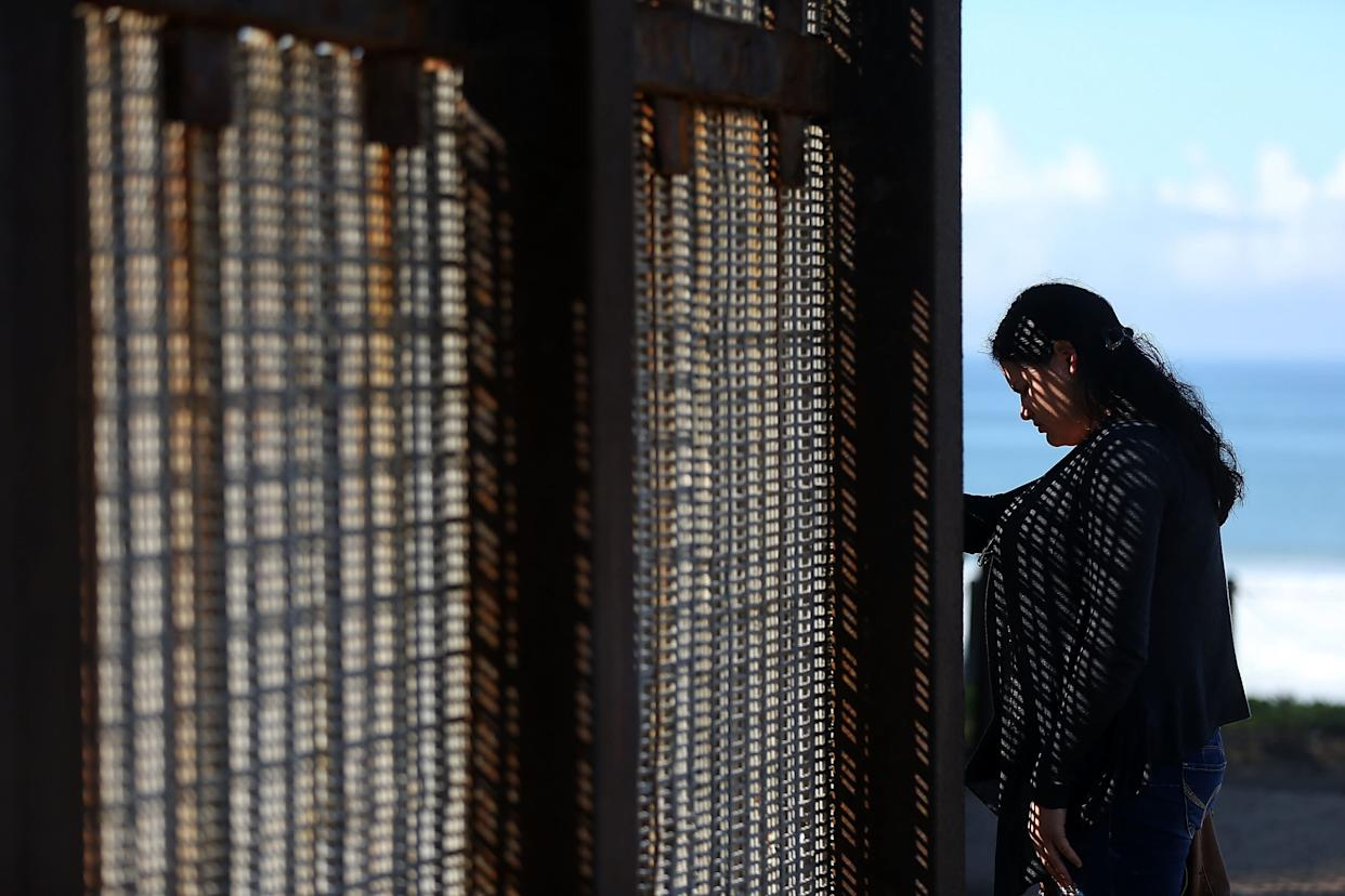A visitor stands next to the U.S.-Mexico border fence at Friends of Friendship Park in San Ysidro, California.