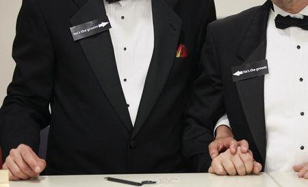 """Two men, both wearing signs that read """"he's the groom"""", hold hands shortly after midnight after getting a civil union when Colorado's civil union law went into effect in Denver"""