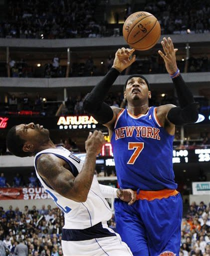 Dallas Mavericks' O.J. Mayo (32) is knocked backwards after taking an elbow from New York Knicks' Carmelo Anthony (7) in the first half of an NBA basketball game, Wednesday, Nov. 21, 2012, in Dallas. Anthony was charged with a foul on the play. (AP Photo/Tony Gutierrez)