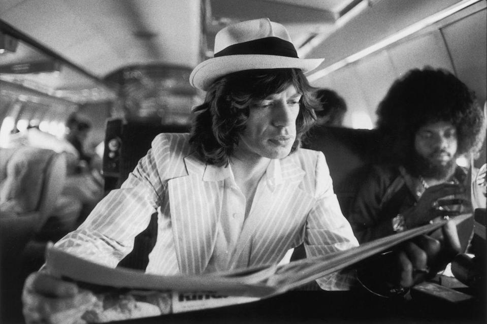 <p>Mick Jagger keeps abreast of current affairs while travelling between concerts in the Rolling Stones' private jet during their 1975 Tour of the Americas. Also aboard is American keyboard player Billy Preston (right).</p>