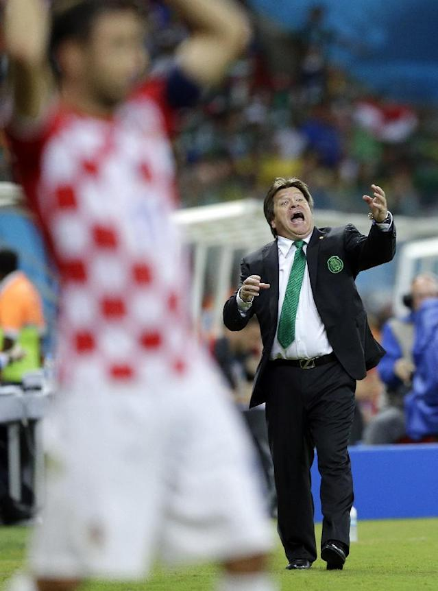 In this Monday, June 23, 2014 photo, Mexico's head coach Miguel Herrera gives instructions to his players during the group A World Cup soccer match between Croatia and Mexico at the Arena Pernambuco in Recife, Brazil. Forget Coach Herrera's success in turning around the troubled Mexican team, which faces off Sunday against the Netherlands after becoming one of the international soccer tournament's biggest surprises. Soccer fans around the global have fallen in love with Herrera's colorful antics, which are often as absorbing as the goal replays. (AP Photo/Ricardo Mazalan)