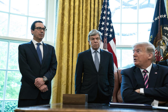 From left, Treasury Secretary Steve Mnuchin and Sen. Roy Blunt (R-Mo.) look on as President Donald Trump speaks at an Oval Office signing ceremony for the Paycheck Protection Program and Health Care Enhancement Act on Friday, April 24, 2020. (Anna Moneymaker/The New York Times)