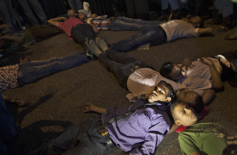 """Egyptian protesters lay on the ground depicting a cross during a march marking the first anniversary of the victims who were killed during clashes with the military police in front of the National State T.V. building, known as Maspero, in Cairo, Egypt, Tuesday, Oct. 9, 2012. Muslim clerics, Christian priests, activists and former liberal lawmakers were among those marching to mark the anniversary of the """"Maspero massacre,"""" referring to the name of the state TV building, where the clashes broke out. (AP Photo/Khalil Hamra)"""